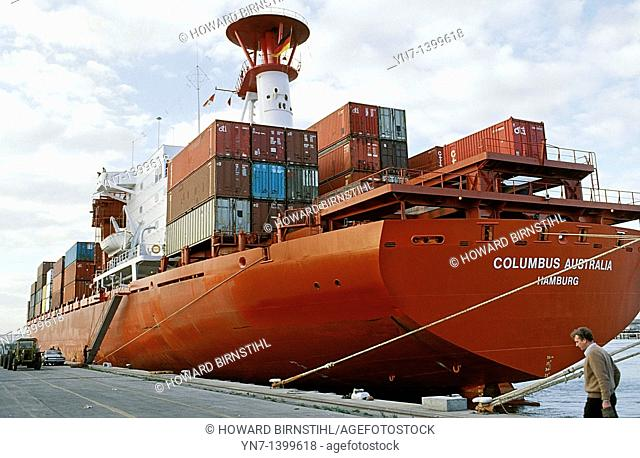Large red cargo vessel fully laden with containers waiting to leave dock