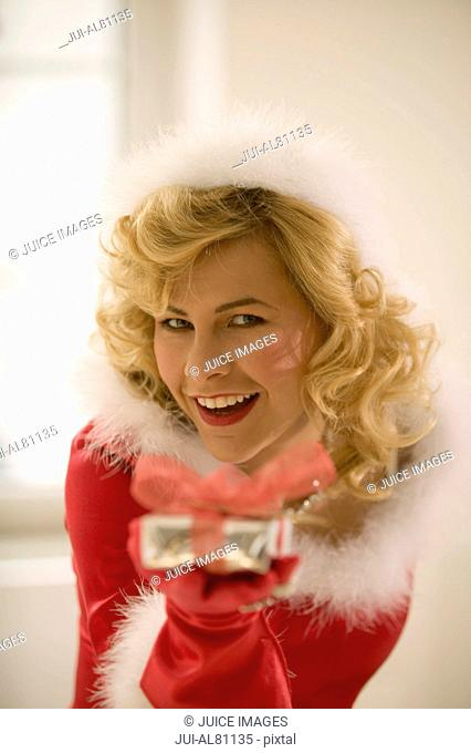 Woman wearing Santa Claus outfit with gift
