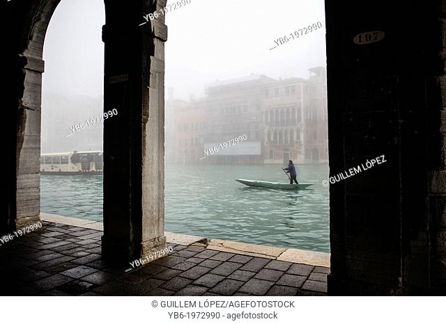 A man rowing along the Grand Canal in Venice Covered in thick fog, Italy