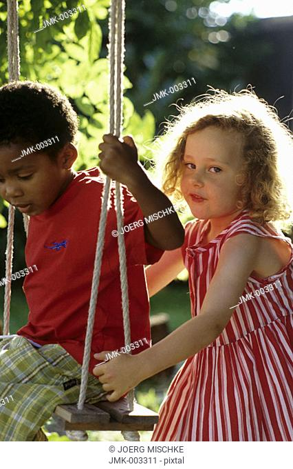 Two little children, a boy and a girl, 1-5 years old, in the garden in summer, the boy sitting on a swing