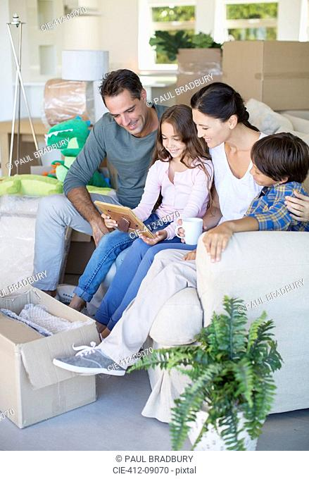 Family looking at picture frame on sofa among cardboard boxes