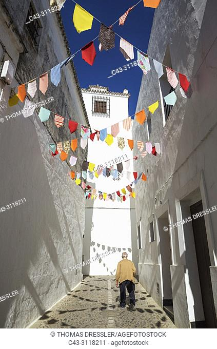 Elderly man in an alley with brilliantly whitewashed houses in the hilltop White Town of Arcos de la Frontera. The little colourful flags are remains of a feast...