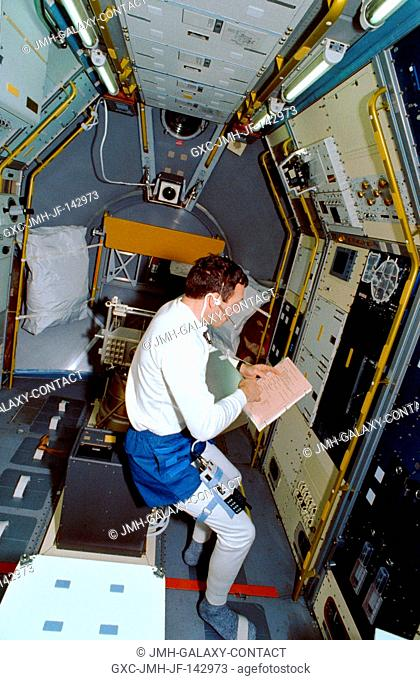 Astronaut David C. Hilmers, mission specialist, looks over a checklist at the Johnson Space Center refrigeratorfreezer, in which perishable samples are stowed