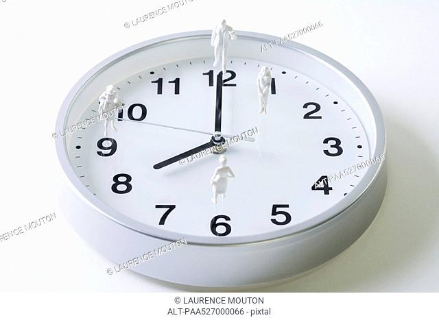 Miniature figures standing on surface of clock