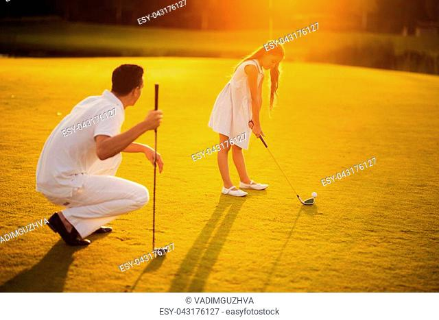 The man is squatting and leans on a golf club, next to a girl in a white dress that bends over the ball and prepares to punch a golf club