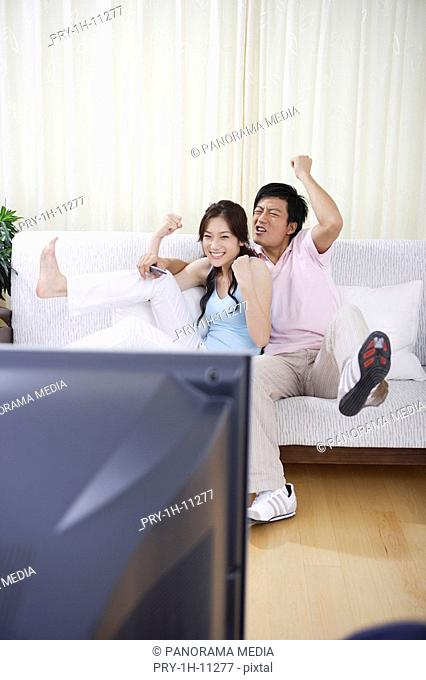 Young couple sitting on sofa and smiling