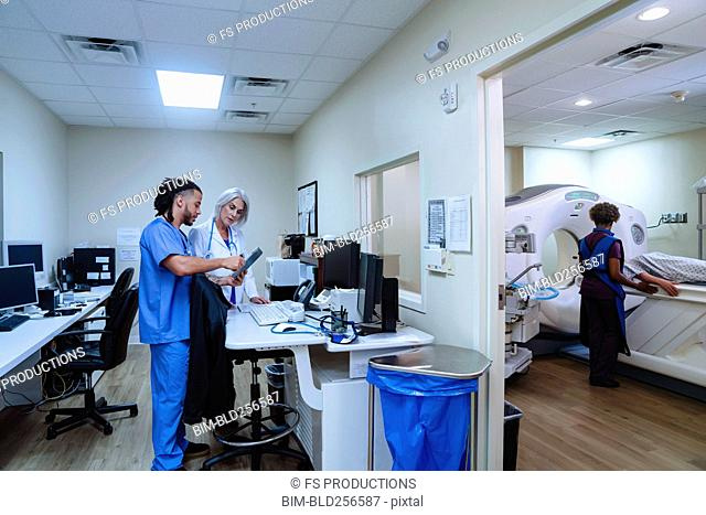 Doctor and nurse discussing digital tablet near scanner