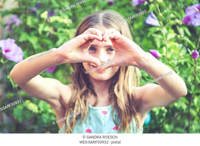 Young girl making a heart shape with her fingers