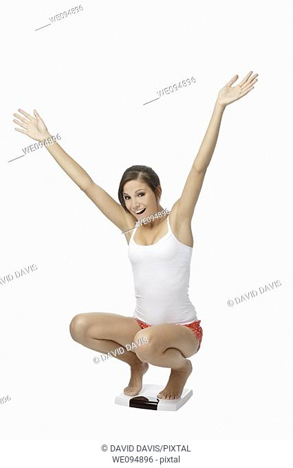 Beautiful Caucasian woman weighting herself and very excited about it