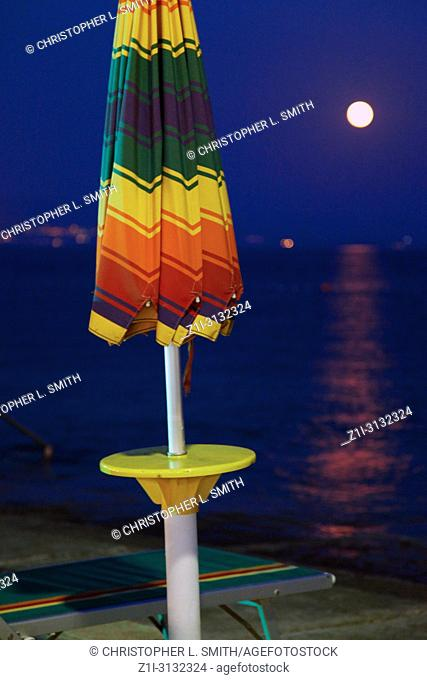 A collapsed beach umbrella besides the water which reflects the light from the moon