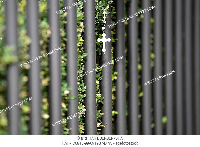 A cross hanging from the fence of the Spanish Embassy in the Tiergarten district of Berlin, Germany, 18 August 2017. Several people were killed and many...