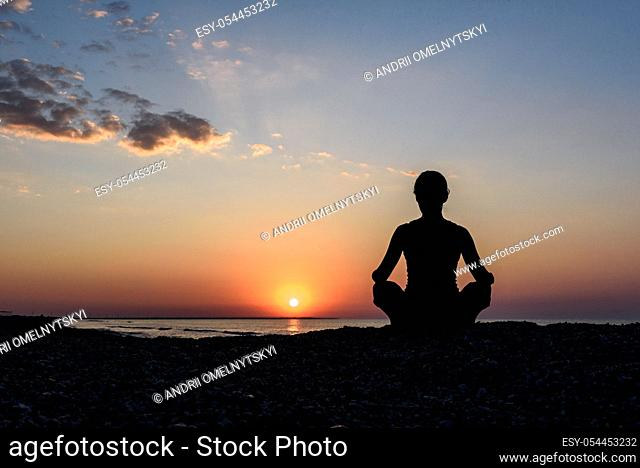 girl on the beach at dawn in yoga assana, silhouette