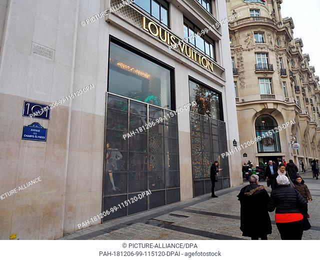 06 December 2018, France (France), Paris: A shop with barred shop windows on the Champs-Élysées boulevard in Paris. Last Saturday there were heavy riots in the...