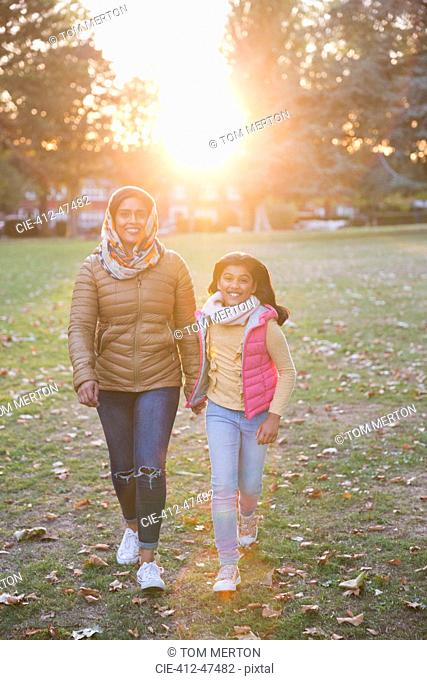 Portrait happy Muslim mother and daughter walking in sunny autumn park