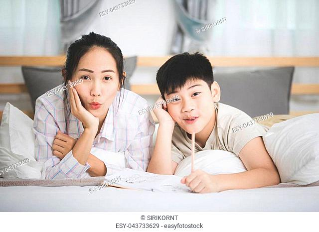 Happy Asian brother and sister rest on the bed and writing with smile face