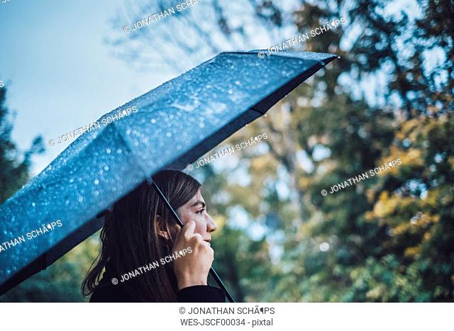 Young woman with wet umbrella in autumnal park