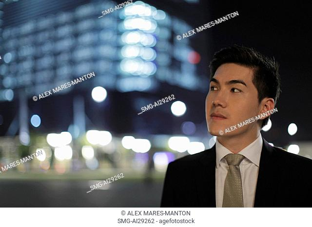 Man wearing a suit looking off, lit buildings in background