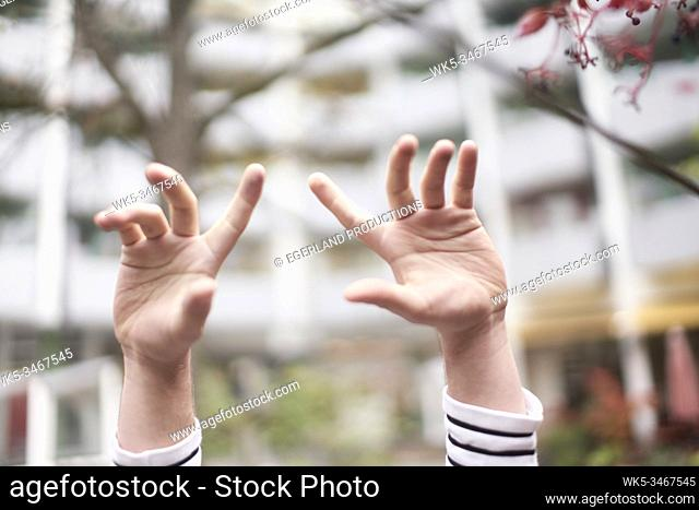 Close-up image of young man's hands raised