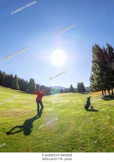 Italy, Veneto, Dolomites, golfer on golf course