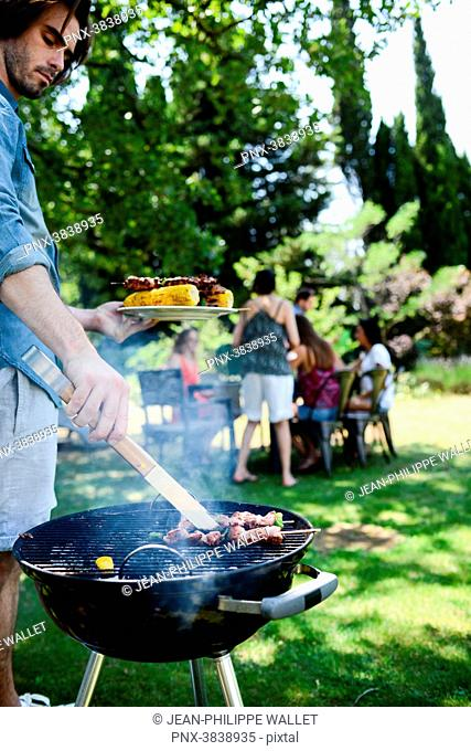 Handsome young man cooking meat in a barbecue party outdoor in the garden during summer holiday