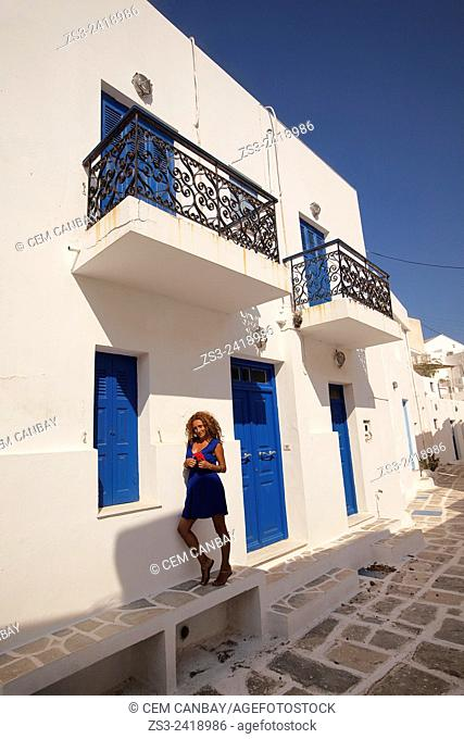 Woman standing in front of a whitewashed Cyclades house in Hora, Serifos, Cyclades Islands, Greek Islands, Greece, Europe