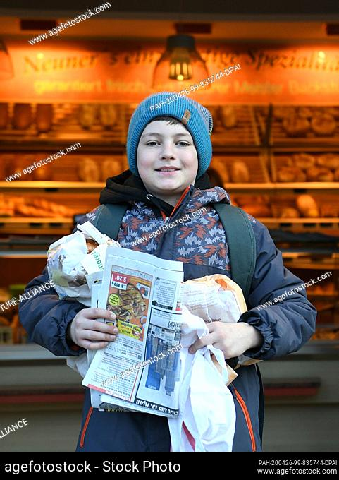 02 April 2020, Bavaria, Oberau: Eleven-year-old Adrian Jais is standing fully packed in front of the bakery after his shopping