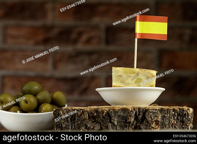 Spanish omelette brochette with spanish flag and olives bowl from below on red brick background