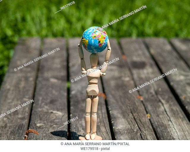 A wooden mannequin with a world ball in his arms. Ecology concept, globalization
