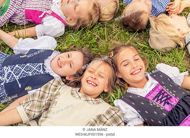 Germany, Saxony, group of children wearing traditional clothes lying on a meadow in circle