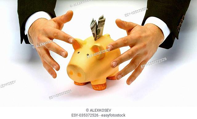 Businessman's hands covering piggy bank