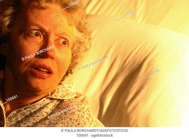 Senior woman afraid in bed