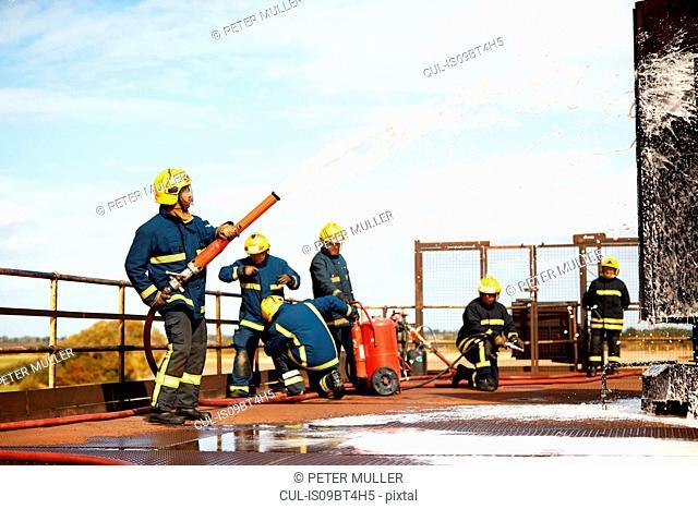 Firemen training, firemen spraying firefighting foam at training facility