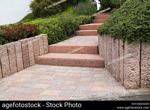 Neat and tidy front yard with solid block steps, decorative gravel and planting