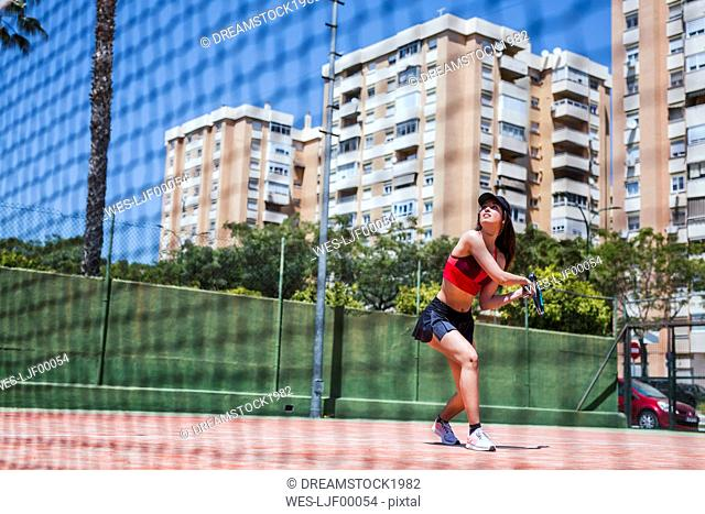 Female tennis player playing on court in the city
