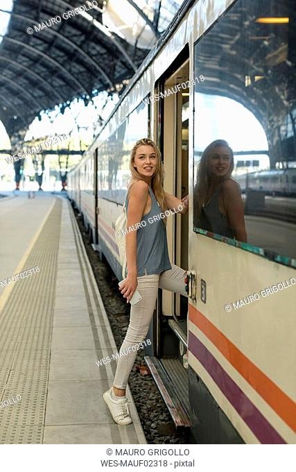 Young woman with cell phone entering a train at the train station