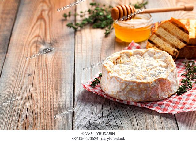 A real Camembert from France with thyme, honey and toasted bread on old wooden rustic table. Soft cheese on a wooden background with copy space