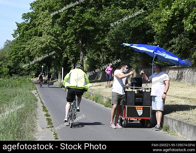 21 May 2020, North Rhine-Westphalia, Cologne: Two friends (r) celebrate Father's Day with their Bollertag and beer. Traditionally the men walk through the...