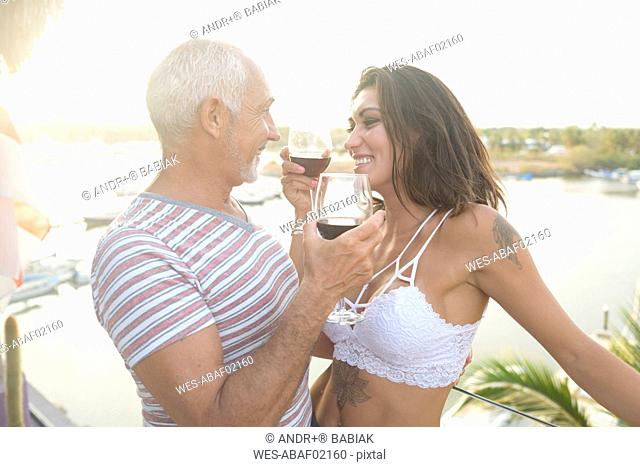 Old man and young woman enjoying red wine on a balcony around sunset