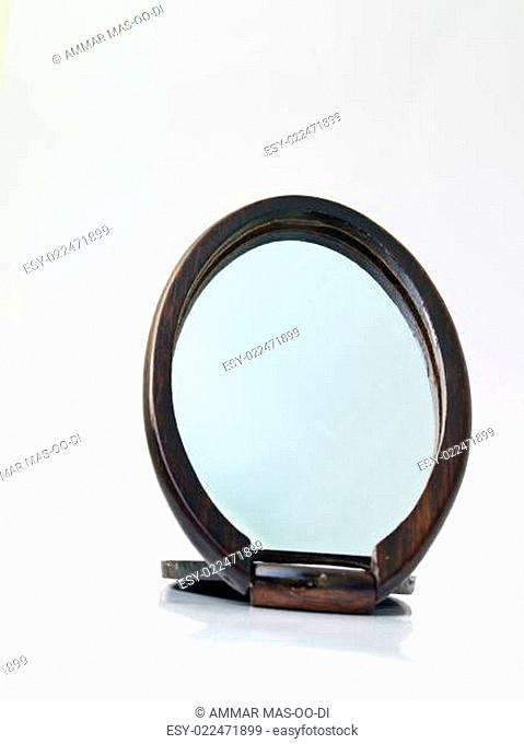 A wooden pocket makeup mirror isolated on white background