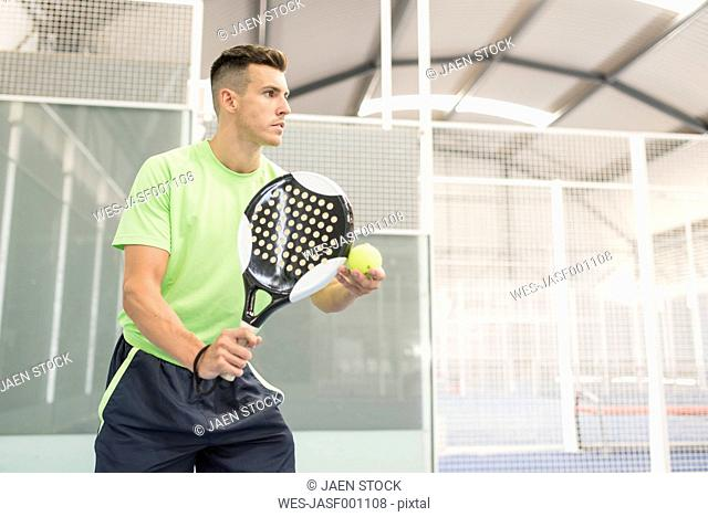 Concentrated paddle tennis player on court