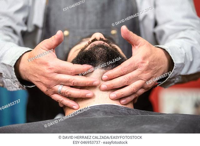 Hair stylist applying after shaving lotion at barber shop