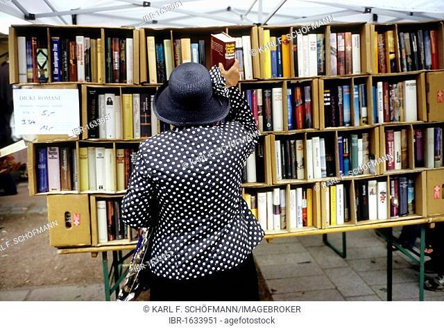 Elderly lady taking a thick novel from store shelf, open-air book market, Koenigsallee, Duesseldorf, North Rhine-Westphalia, Germany, Europe