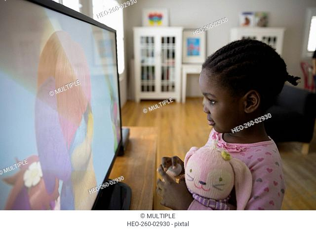 Girl with stuffed doll watching cartoons at TV
