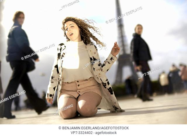 unrestrained woman kneeling and dancing outdoors in public in city next to tourist sight Eiffel Tower, being watched by passersby, enjoying herself, at Espl