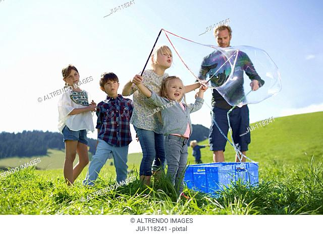 Father And Children Making Giant Bubbles In Countryside