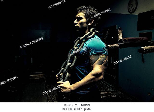 Weightlifter in dark gym, chain around his neck