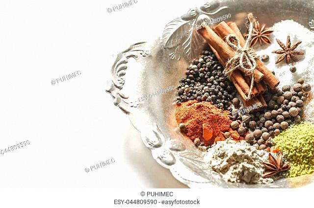 A variety of Oriental spices on a beautiful plate,isolated on white background, concept of spicy food and spices