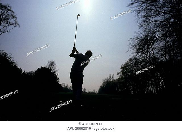 Silhouette of a golfer tees off on a golf course