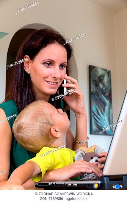 Eine junge Frau arbeitet zu Hause im Heimbüro und hat ein Kind an ihrer Seite