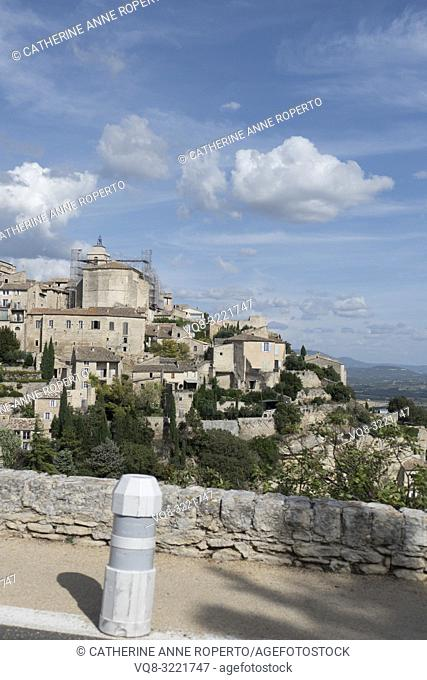 Sky blue day with puffy white clouds and long shadows, tumbling down the hillside past the historic mountain town of Gordes in the Vaucluse